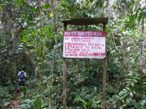 "A sign ""Propiedad Privada"" next to rainforest"