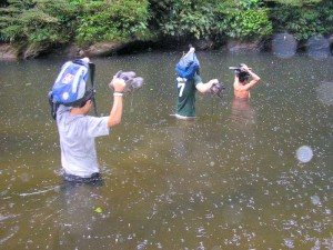 Three guys walking into a river and holding their backpacks