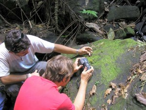 Two people with an old digital camera on a rock next to a yellow frog