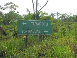"A sign that reads ""Tarapoto / Yurimaguas"" with arrows in each direction"